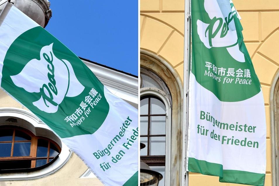 Eine weiße Taube vor grünem Hintergrund: Vor den Rathäusern in Löbau und Zittau haben am Montag die Flaggen geweht.