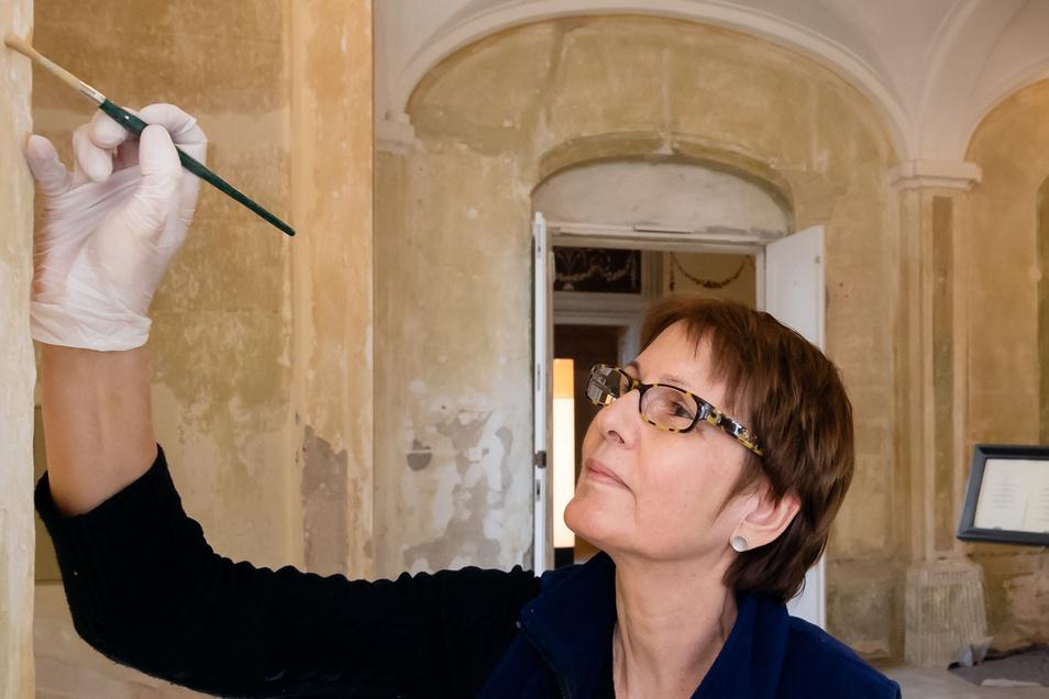 Restauratorin Heike Pfund arbeitet an einer Säule in der Eingangshalle des Rammenauer Schlosses. Voraussichtlich bis November dieses Jahres sollen die Arbeiten hier und im Treppenhaus abgeschlossen werden.