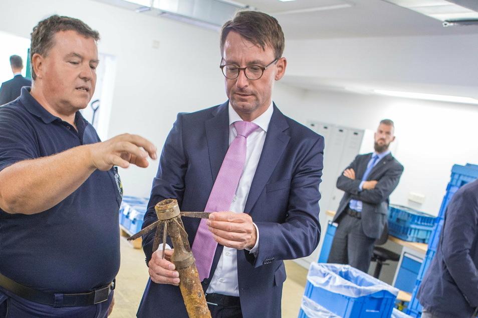 Sprengmeister Holger Klemig (l.) vom Kampfmittelbeseitigungsdienst führt bei einer Visite im August 2018 in Zeithain Sachsens Innenminister Roland Wöller (CDU) besondere Funde vor.