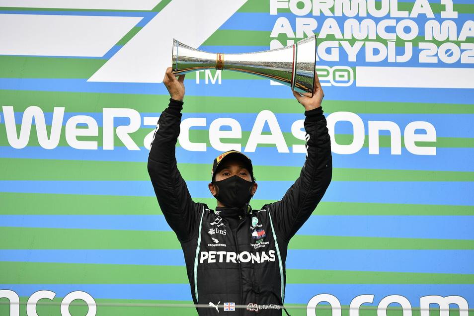 Lewis Hamilton freut sich über seine  Trophäe