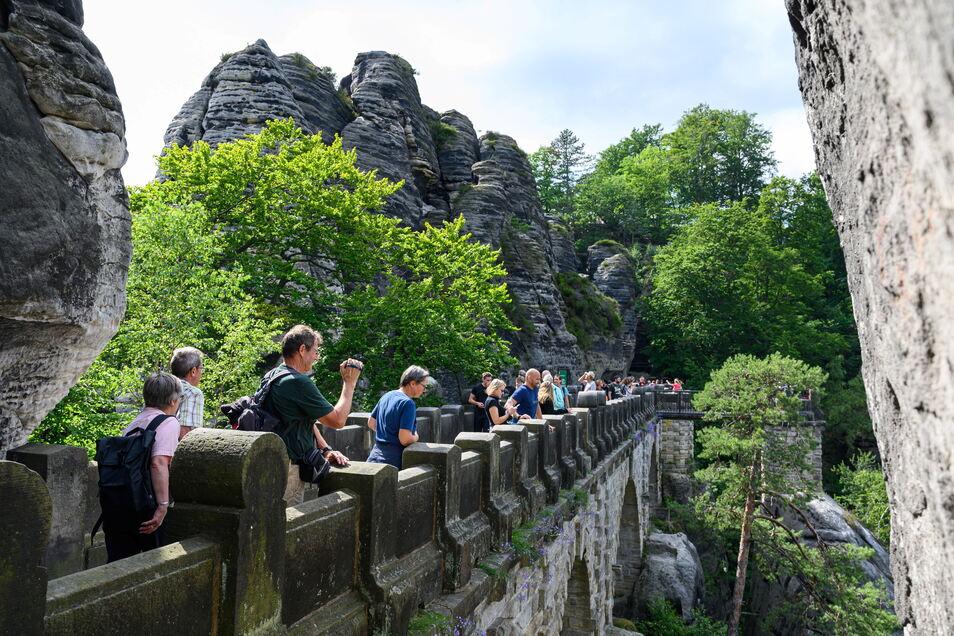 Touristen laufen im Nationalpark Sächsische Schweiz über die Basteibrücke. Im Hintergrund ist der Lilienstein zu sehen.