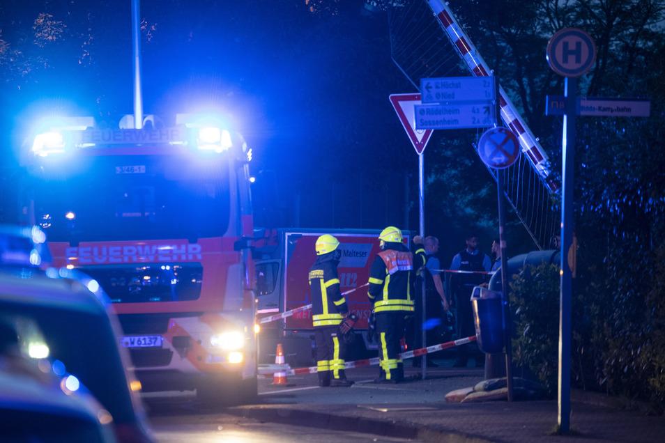 Polizisten und Feuerwehrleute stehen nach einem tödlichen Verkehrsunfall neben den Gleisen.