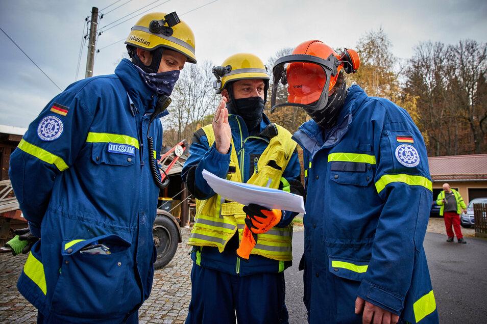 THW-Einsatzleiter Mirco Kammann (Mitte) bespricht mit Mitarbeitern den bevorstehenden Transport.