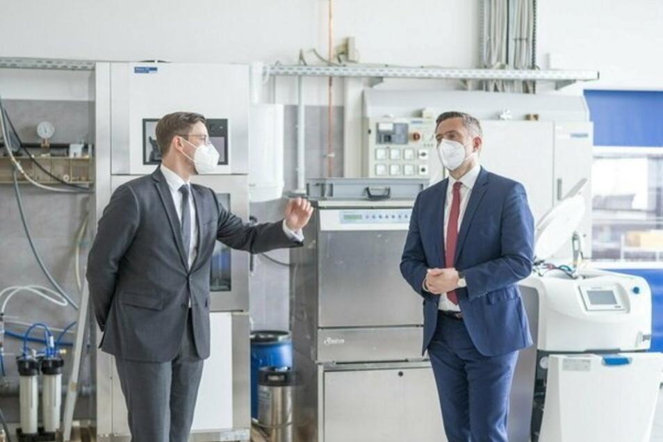 Paul Hartmann (links) zeigt Minister Dulig seine Wasseraufbereitungsanlagen für das Gesundheitswesen. Das Unternehmen in Hainichen hat Fördergeld für Software und Schulungen bekommen.