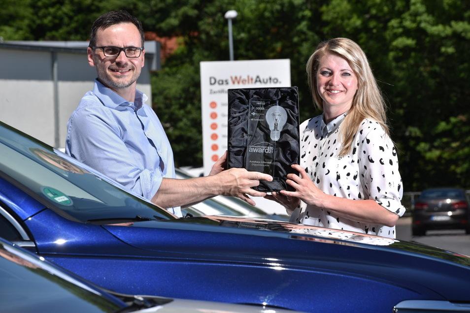Inhaber Daniel Liliensiek und die Gebrauchtwagenverantwortliche Anne Papenfuß stehen mit dem Pokal auf dem Gebrauchtwagenplatz des Autohauses Liliensiek in Dipps.