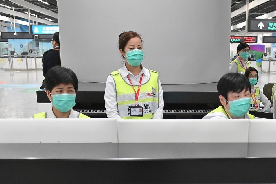 Mitarbeiter des Hongkonger Gesundheitswesens untersuchen am Bahnhof Reisende auf ihren Gesundheitszustand hin.