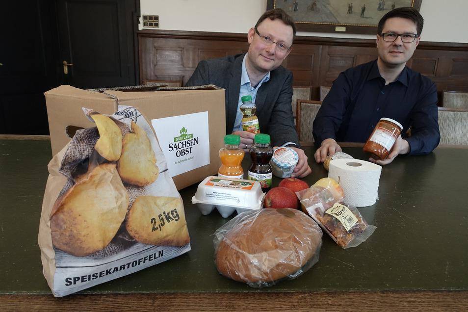 """Mathias Möbius (links), Vorstand Obstland AG, und Oberbürgermeister Sven Liebhauser mit einer ausgepackten """"Herzensbox"""". In der sind Lebensmittel aus der Region verpackt."""