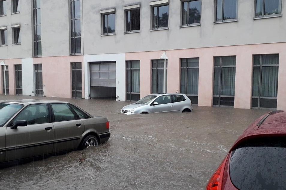 Nach einem Unwetter mit Starkregen stehen Autos auf einem Parkplatz im Wasser.
