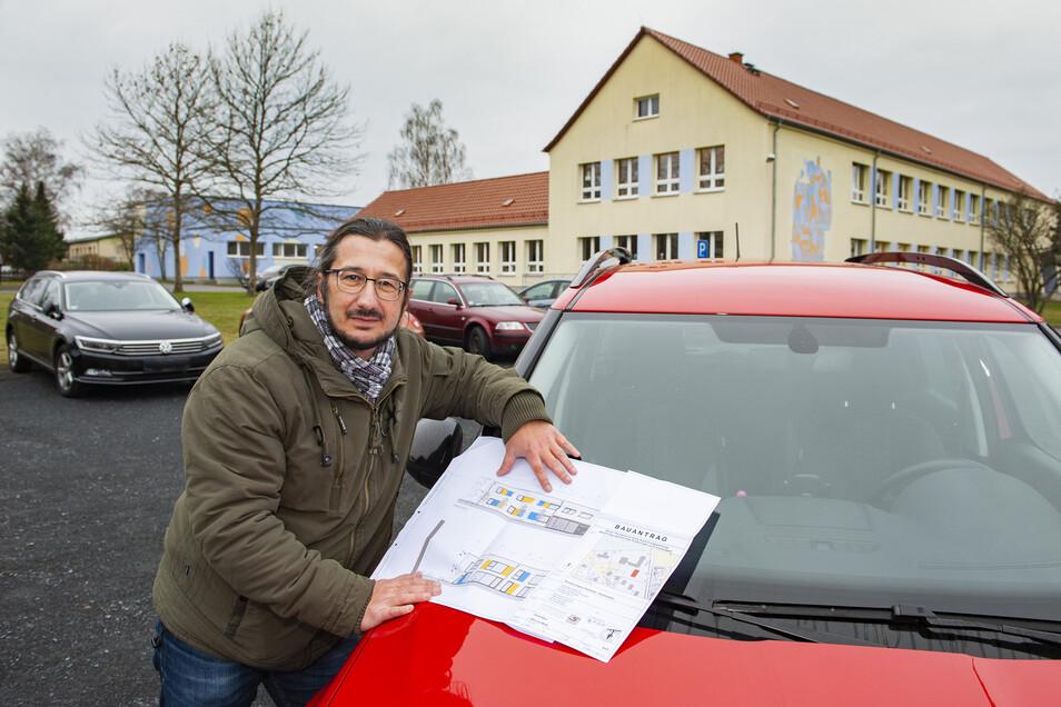 Thiendorfs Bürgermeister Dirk Mocker zeigt an der Grundschule Ponickau den Plan fürs künftige Hortgebäude.
