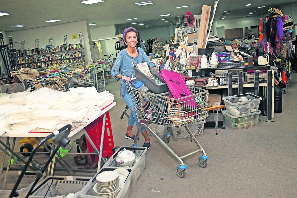 Blick in die Secondhandhalle Riesa: Mitarbeiterin Manuela Jobst bringt gerade neue Waren aus einer Haushaltsauflösung heran, die nun aus- und in die Regale einsortiert werden müssen.