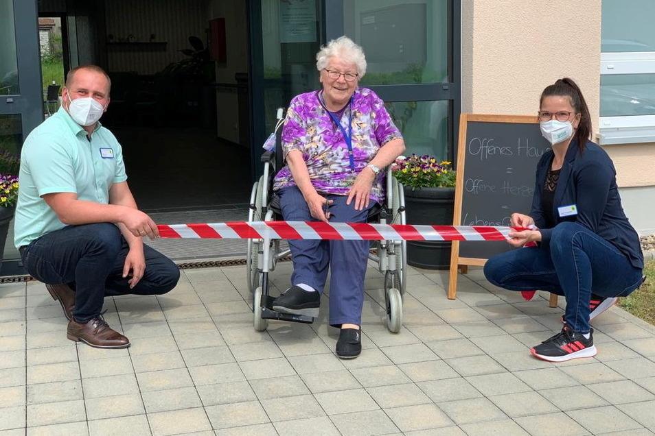 Die Tür wird symbolisch wieder freigegeben: Azurit-Bewohnerin Margit Hartmann freut sich auf die Lockerungen der Besuchsregelungen. Links ist Hausleiter Stefan Lux zu sehen, rechts Betreuungsleiterin Susann Doberentz.