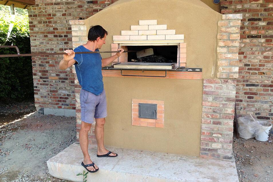 Tobias Zschieschick, der Geschäftsführer der Krabat-Mühle Schwarzkollm, nach einem Probebefeuern des Holzbackofens vor dem Brotbackhaus. Den stählernen Brennstoffschieber, hat er jetzt nach historischem Vorbild vom Dorfschmied anfertigen lassen.