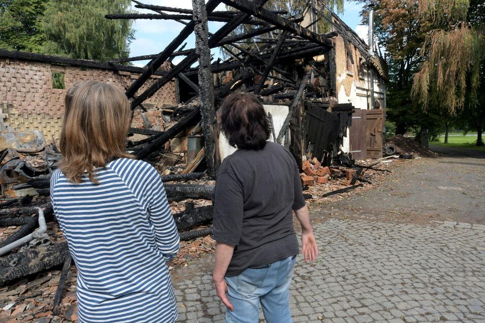 Heidi Melde und Rita Held stehen vor den Trümmern der angebrannten Scheune ihres historischen Dreiseitenhofs in Saalendorf im Zittauer Gebirge.