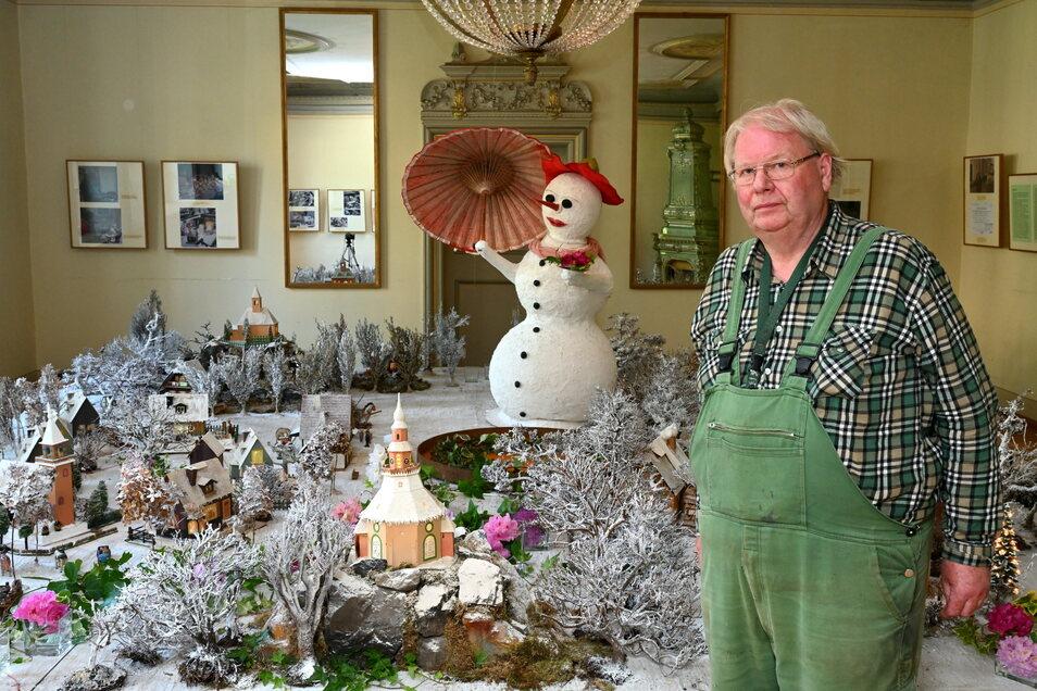Matthias Riedel steht im Salon vor der winterlichen Landschaft mit Lichterhäusern aus Olbernhau. Die gehörten zur Weihnachtsausstellung, die aber keiner sehen durfte. Nun sind für kurze Zeit noch einige der seltenen Leihgaben zu besichtigen.