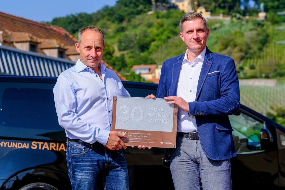 Autohändler Torsten Hammer (l.) bekommt als Anerkennung für seine 30-jährige Vertragspartnerschaft mit Hyundai eine Urkunde sowie eine silberne Plakette von Sebastian Braun, Hyundai- Distriktleiter Vertrieb Region Sachsen, überreicht.