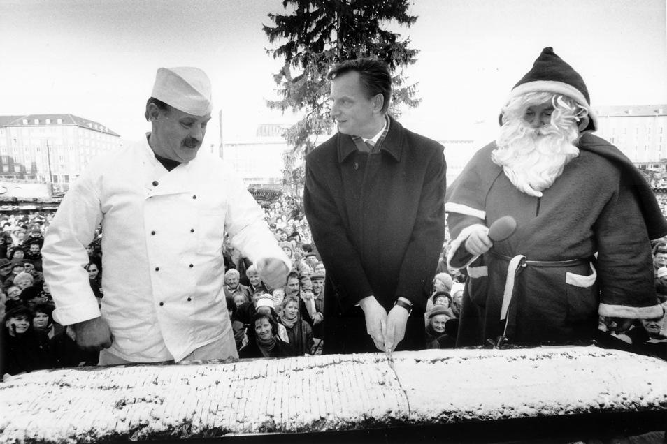 1995: Oberbürgermeister Herbert Wagner schneidet den Stollen an. Der Bäckermeister gibt gute Ratschläge und der Weihnachtsmann darf immerhin das Mikro halten.