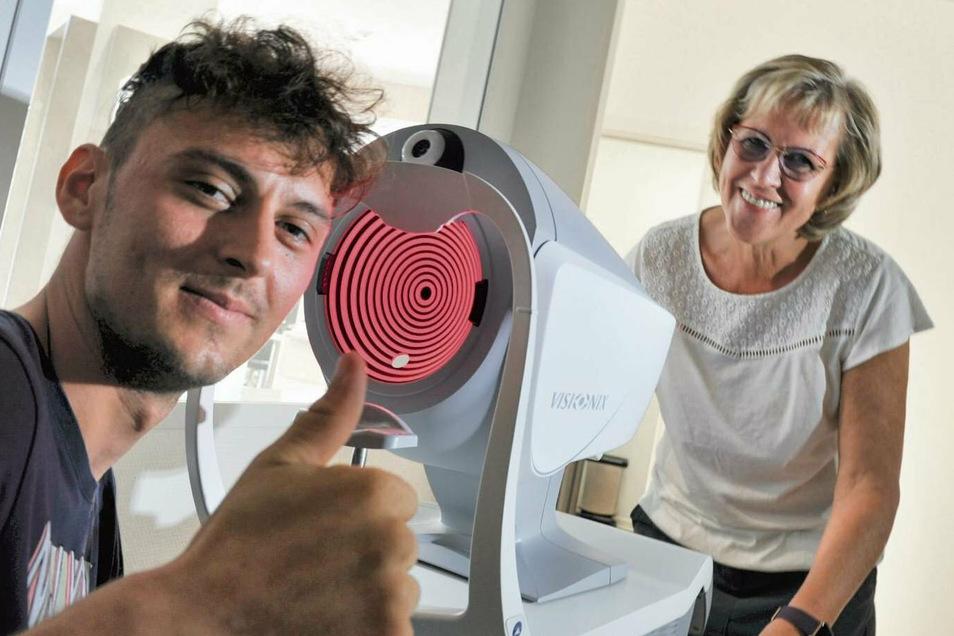 Optikerin Angela Miatke bringt Azubi Artem Galaktionov Kenntnisse und Fertigkeiten ihres Berufs bei, auch die Augendruckmessung mit dem neuen Visonix-Gerät.