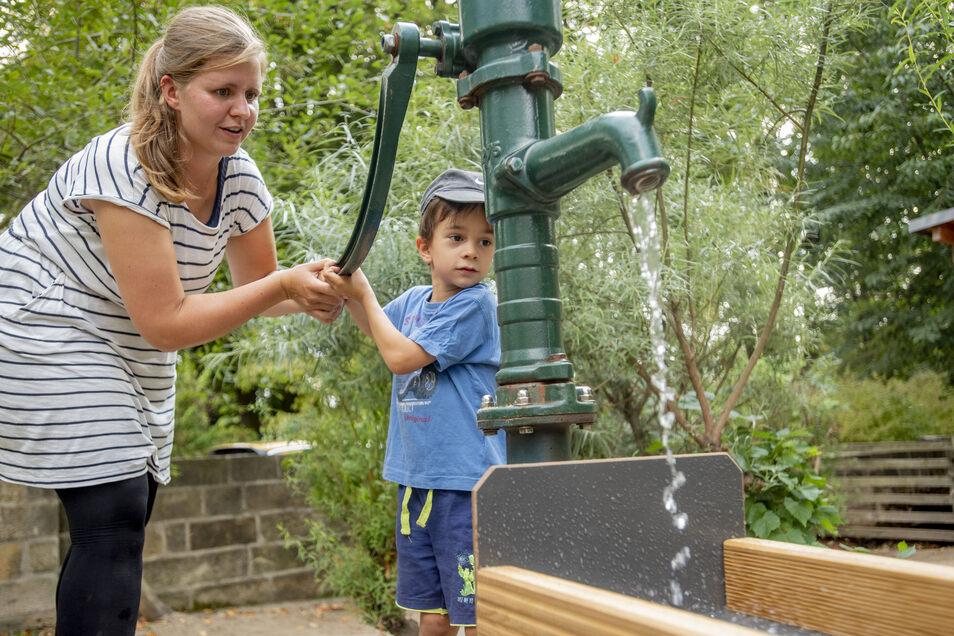 """Und kräftig pumpen: In der Kita """"Baumhaus"""" in Radeberg nahmen Jakob und Kita-Mitarbeiterin Katharina Hempel die neue Matschanlage in Betrieb. Anschließend wurde eine große Wasser-Party gefeiert."""