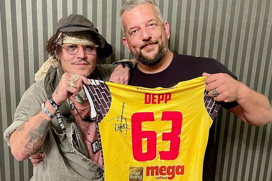 Johnny Depp (l.) und der in Suhl lebende Musiker Alexander Becker halten zusammen ein Trikot des Volleyball-Bundesligisten VfB Suhl.