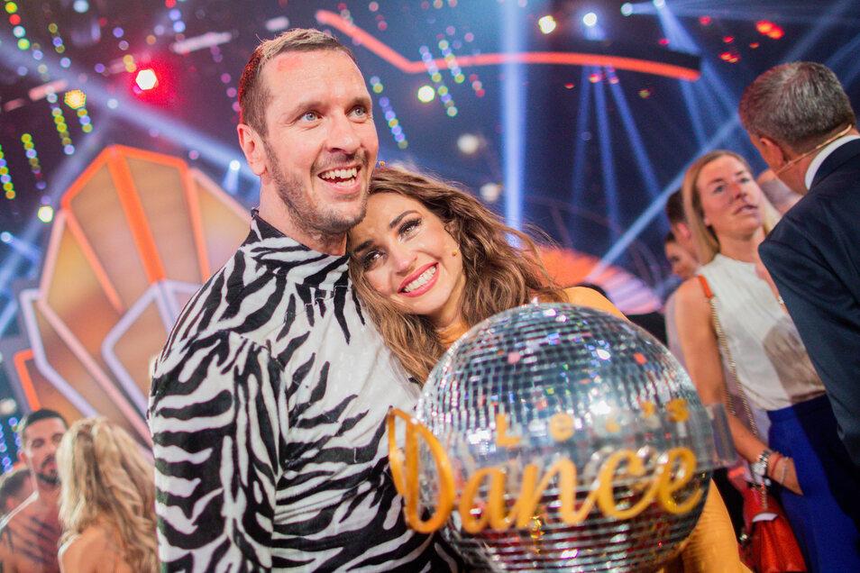 Pascal Hens, ehemaliger Handballer, und Ekaterina Leonova, Profitänzerin, freuen sich mit dem Pokal über den Sieg.