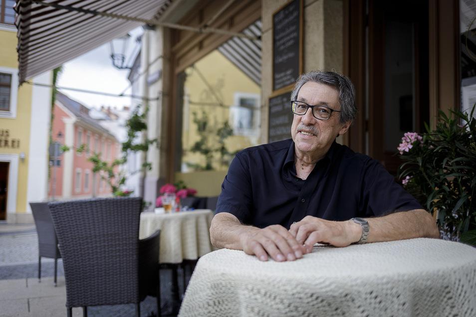 Johannes Witoschek sitzt vor dem Nikolai-Café. Sein neues Lokal befindet sich gleich gegenüber der Jesus-Bäckerei.