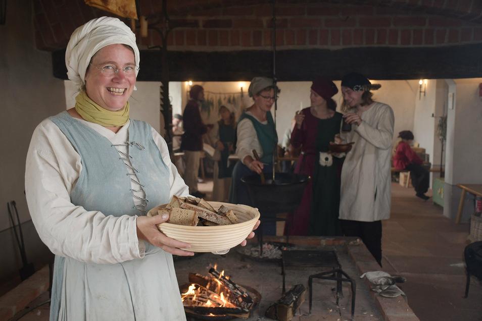 Anja Kiessling vom Team Burgalltag zeigt eine Schüssel mit frisch gebackenem Brot, das sie in Scheiben geschnitten hat. Auch eine deftige Suppe wurde gekocht.