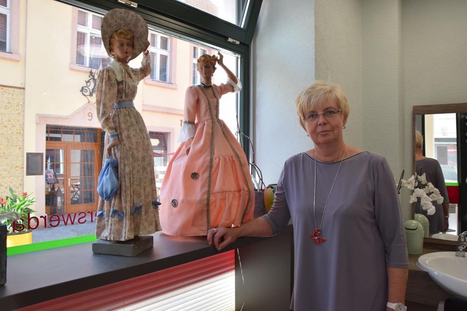 Renate Musiol mit den beiden Puppen, die Kleider im Biedermeier- und im Rokoko-Stil tragen.