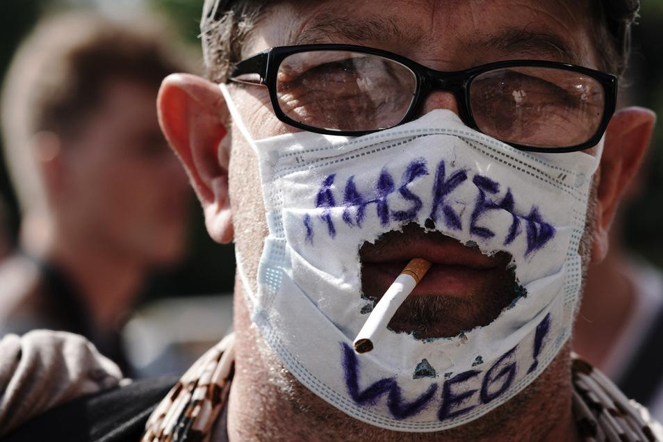 """""""Masken Weg!"""" steht auf dem """"Mundschutz"""" eines Teilnehmers einer Demonstration gegen die Corona-Maßnahmen in Berlin."""