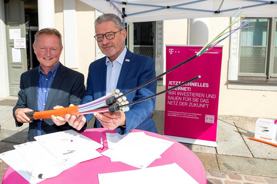 Rainer Frank (links) von der Telekom und Oberbürgermeister Stadt Pirna Klaus-Peter Hanke unterzeichnen eine gemeinsame Absichtserklärung zum Ausbau des Glasfasernetzes.