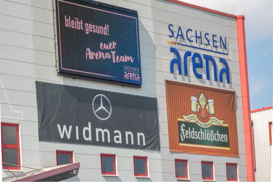 Bleibt gesund: Solche Botschaften gab es im April von der Fassade der Sachsenarena. Nach monatelanger Schließung startet die Riesaer Halle nun wieder mit einer Veranstaltung.