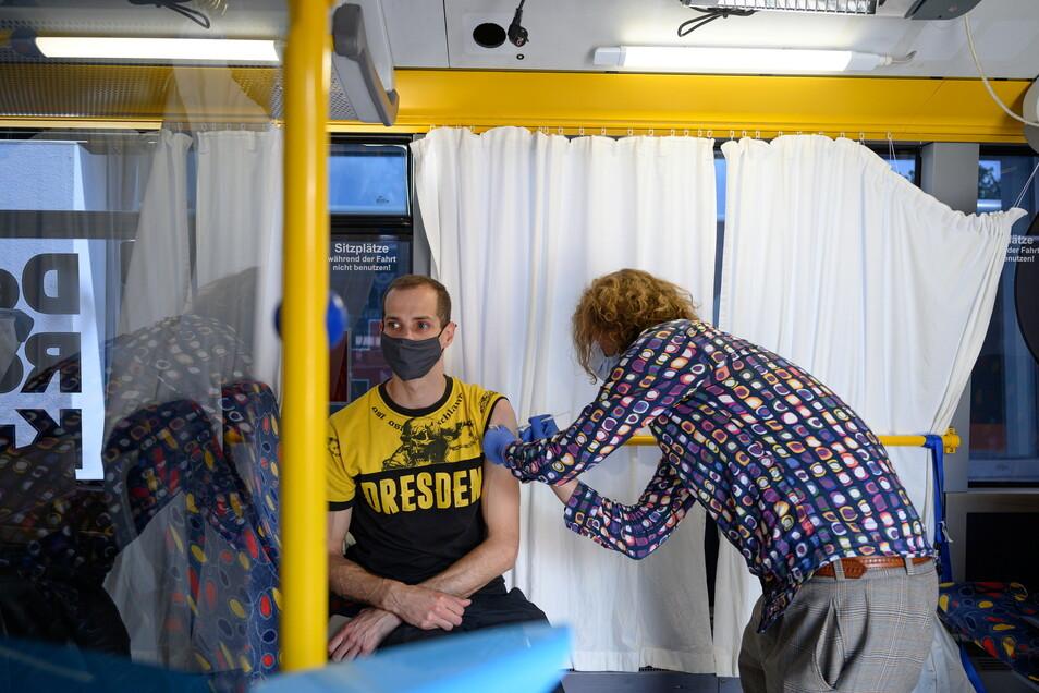Ein Dynamo-Fan lässt sich zum Auftakt der gemeinsamen Impfaktion der Landeshauptstadt und des Deutschen Roten Kreuzes (DRK) zum Start der neuen Saison für Dynamo Dresden gegen das Coronavirus impfen.