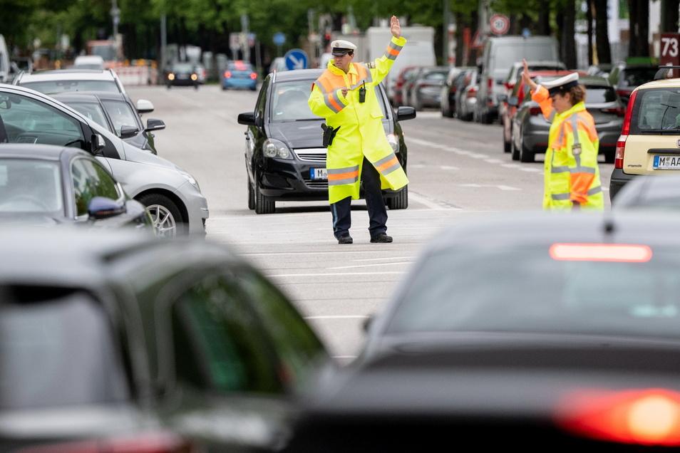 Polizisten regeln auf einer Münchener Kreuzung den Verkehr, nachdem dort die Stromversorgung der Ampeln ausgefallen war.