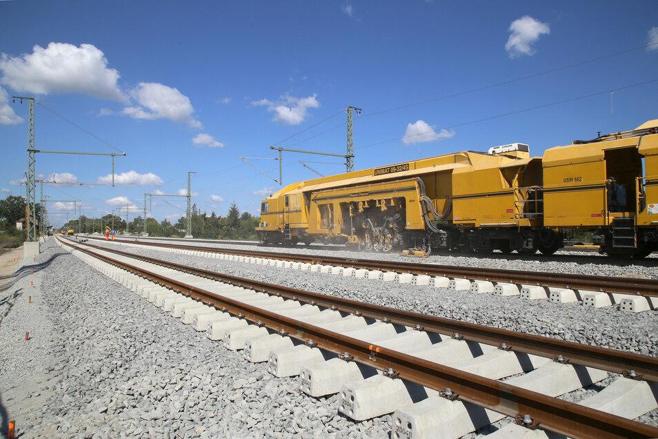 """Die Brücke am Bahnübergang Krone, die eigentlich eine Unterführung ist, ist praktisch fertig. Der """"gelbe Zug"""" ist die Stopfmaschine, die das Gleisbett verdichtet. Künftig fahren oben """"richtige Züge"""", unten ist Platz zur Durchfahrt für Autos."""