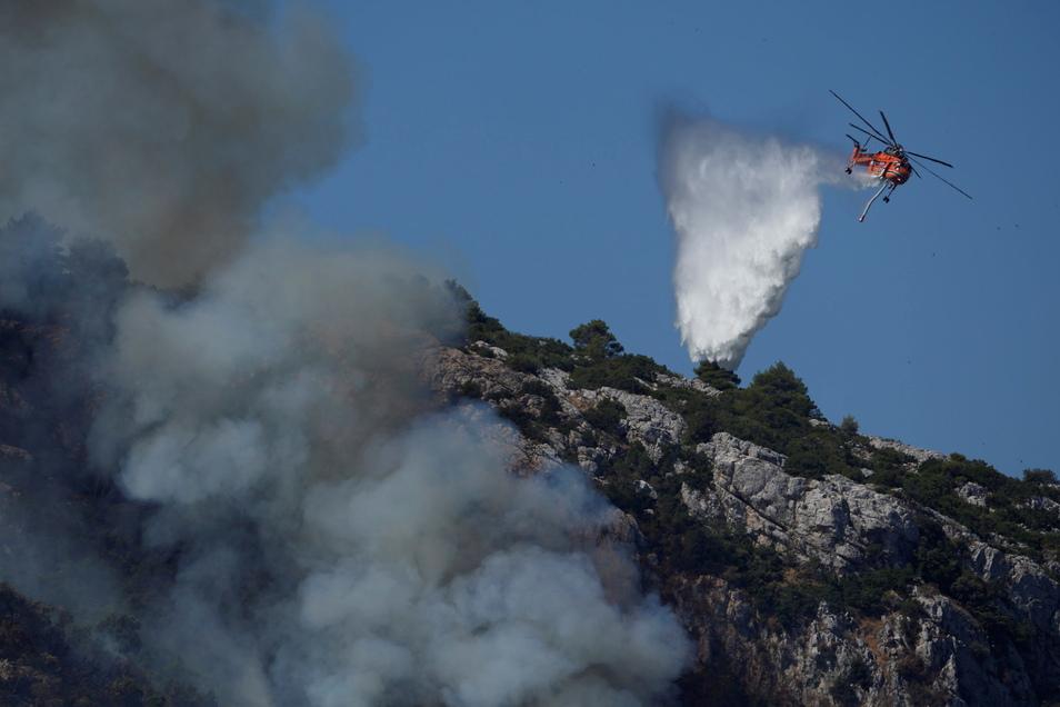 Ein Hubschrauber wirft über einem Feuer in der Nähe des Dorfes Malakasa nördlich von Athen Wasser ab.