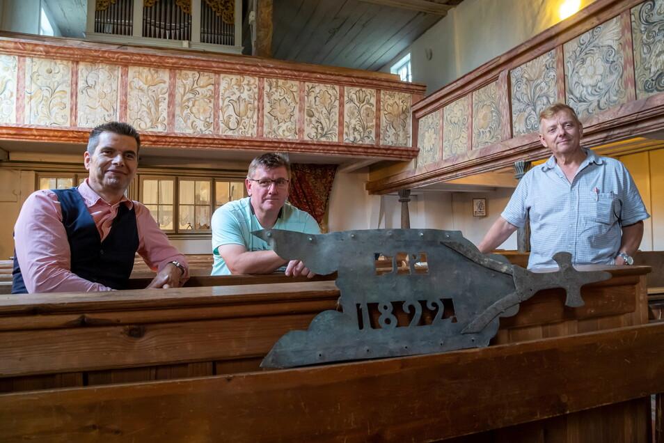 Jens Drängner, Hagen Gano und Wolfram Schulze (v.l.) sind alle drei Petershainer und zählen mit zu den Gründungsmitgliedern des Kirchbauvereins in Petershain. Im Vordergrund die Kirchturmfahne von 1822 die auf einem Dachboden gefunden wurde.