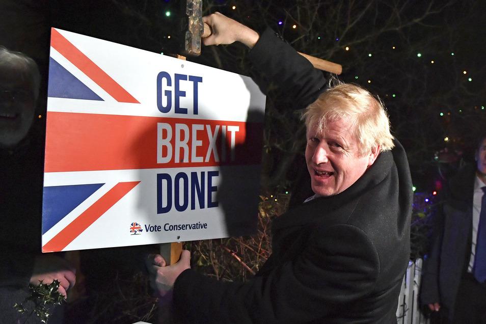 Boris Johnson, Premierminister von Großbritannien, bringt am letzten Tag des Wahlkampfes ein Schild mit seinem Wahlslogan im Garten eines Anhängers an.
