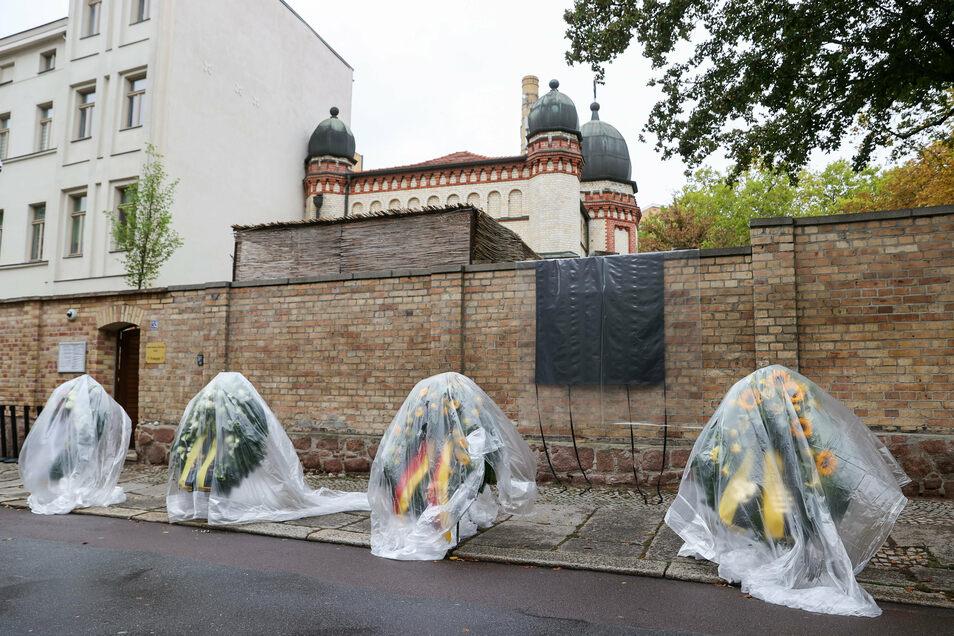 Die Kränze für den Gedenktag an den Anschlag stehen mit Regenfolie überzogen vor der Synagoge.