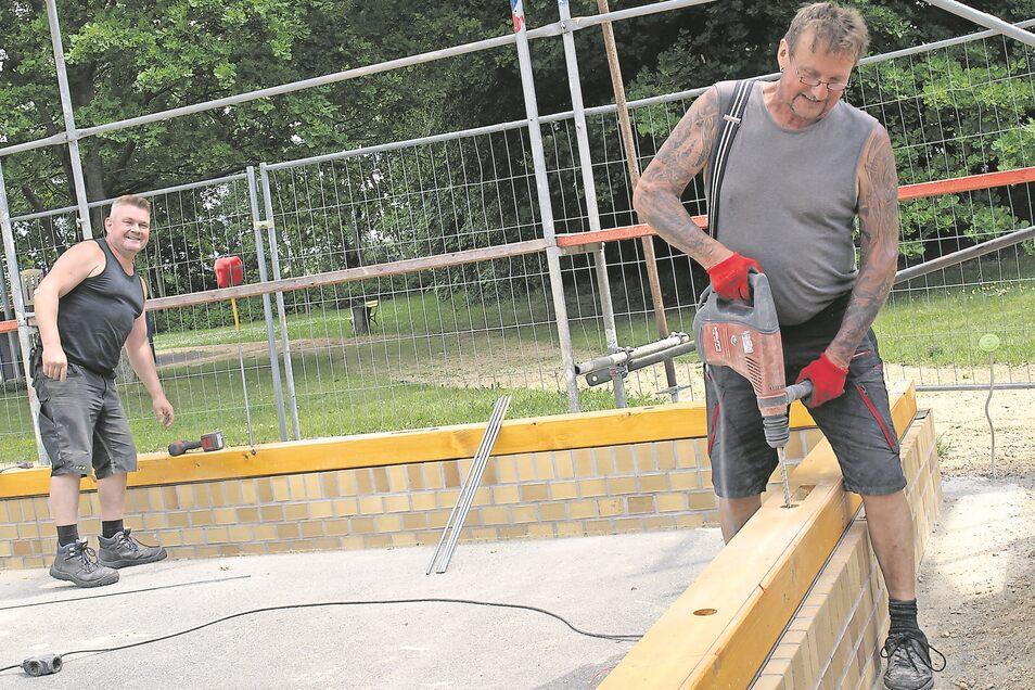 Jens Pannasch (li.) und Heinz Steinke von der Holzbaufirma Rösch bringen die Fußschwellen an, auf die Fachwerkwand und Dachkonstruktion gesetzt werden.