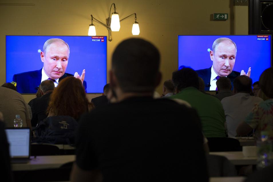 """Wladimir Putin ist auf einem Bildschirm zu sehen, während er bei seinem jährlichen TV-Auftritt in der Sendung """"Direkter Draht"""" Fragen von Zuschauern beantwortet."""
