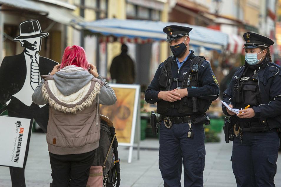 Polizeiobermeister Sebastian Kreß (2.v.r.) und Kollegin bei der Masken-Kontrolle in Pirna: Reden, Vertrauen schaffen, Hinweise geben.