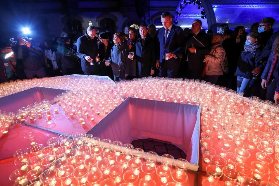 Leipzigs OB Burkhard Jung (l-r, SPD), Michael Kretschmer (CDU), Ministerpräsident von Sachsen, und Vitali Klitschko, OB von Kiew, stellen Kerzen in eine überdimensionale ·89 auf dem Nikolaikirchhof.
