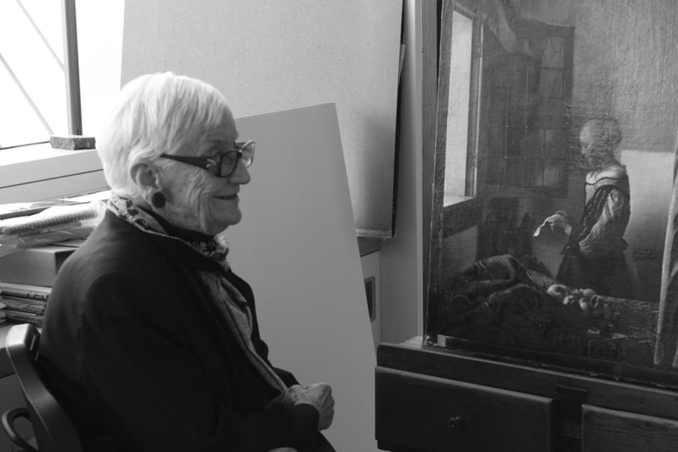 """Annaliese Mayer-Meintschel, im Hintergrund das Gemälde """"Brieflesendes Mädchen"""" von Jan Vermeer."""