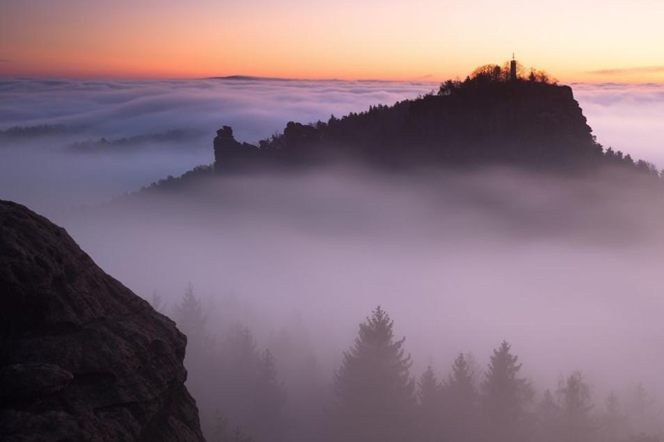 Eine einsame Insel im Meer: der Papststein im morgendlichen Nebel.