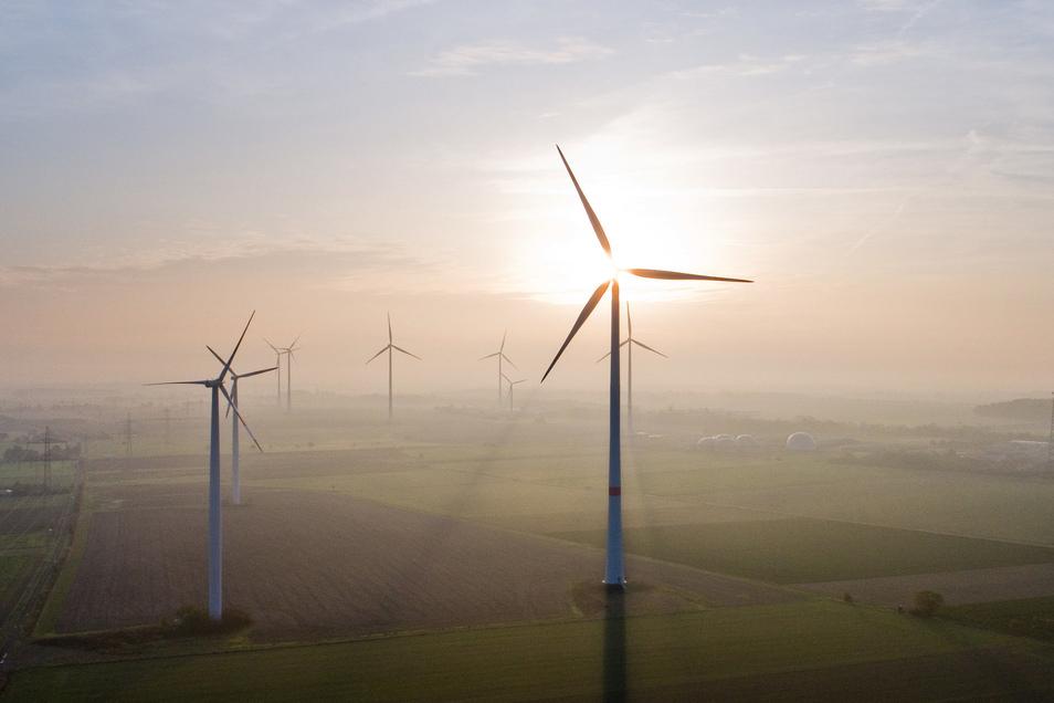 Wirtschaftsfaktor mal ganz idyllisch: Die aufgehende Sonne steht hinter einem Windrad.