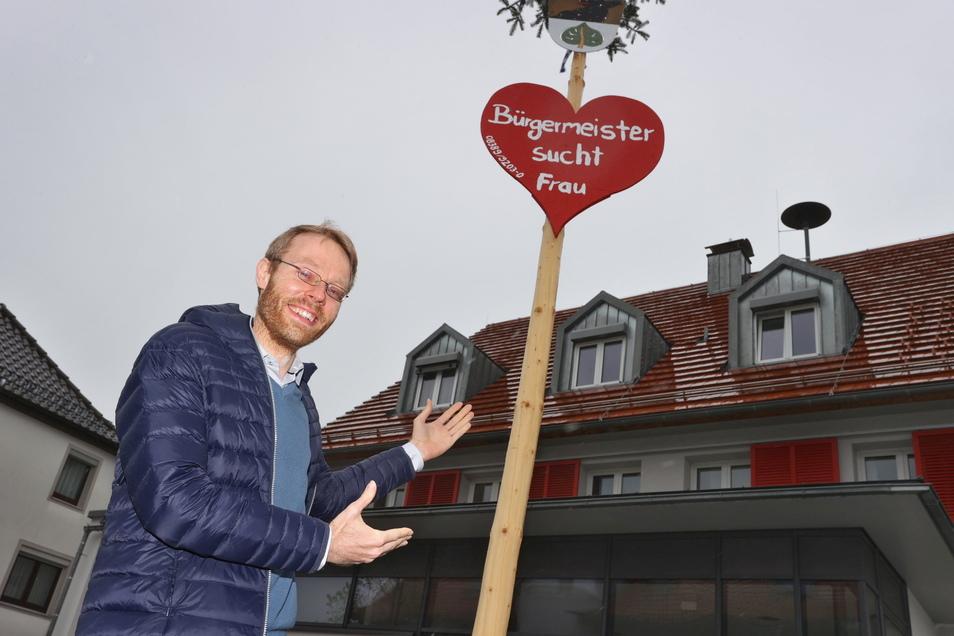 """Jörg Aghte, Bürgermeister der Gemeinde steht vor der """"Kontaktanzeige"""" am Maibaum."""