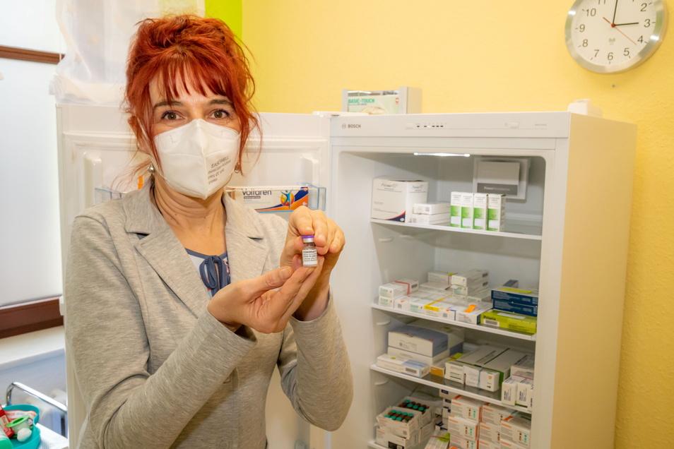 Ärztin Sylvana Kretschmar zeigt in ihrer Praxis in Niesky eine Ampulle mit Impfserum für sechs Impfdosen gegen Corona.