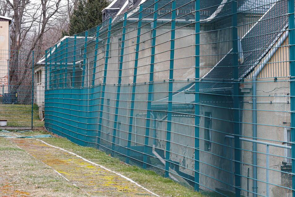 Mit dem Hang bewegt sich auch der Zaun des Sportplatzes in Löbau auf das weiter unten stehende Haus zu. Vor dem Zaun die derzeit nicht nutzbare Weitsprunganlage.