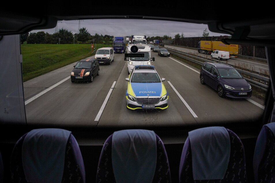 Die Autobahnpolizei folgt dem Bus mit einem Streifenwagen, um Lasterfahrer sofort zu stoppen, wenn sie zum Beispiel dabei beobachtet wurden, als sie während der Fahrt mit ihrem Handy beschäftigt waren.