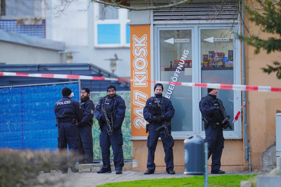 Einsatzkräfte der Polizei stehen vor einem der Tatorte, einem Kiosk in Hanau.