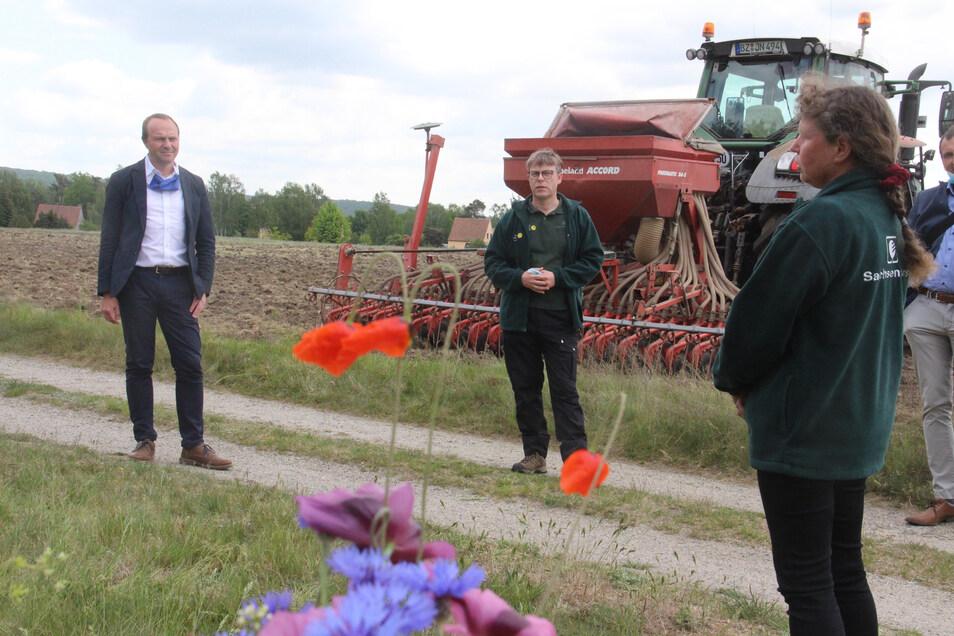 Sachsens Umwelt- und Landwirtschaftsminister Wolfram Günther (l.), wird von Biosphärenreservatsleiter Torsten Roch und der Projektverantwortlichen Eva Lehmann über Details des Projektes zur Rettung von Insekten-Arten informiert.